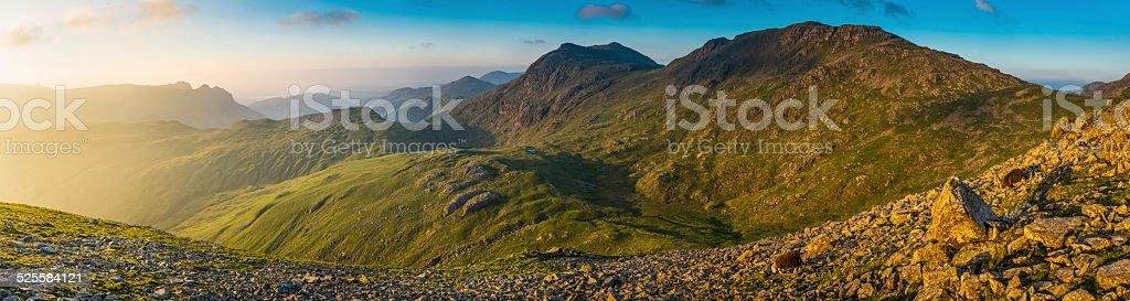 Golden light filling mountain valley panorama Lake District fells UK stock photo