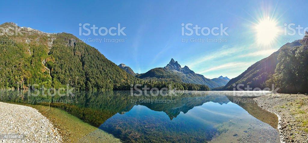 Golden light on beautiful reflection of a misty lake panorama stock photo