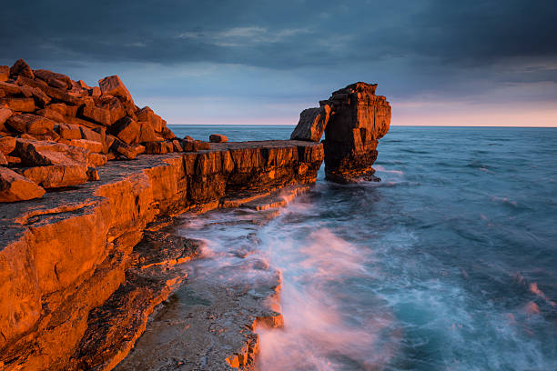 golden light on pulpit rock - pulpit rock dorset stock photos and pictures
