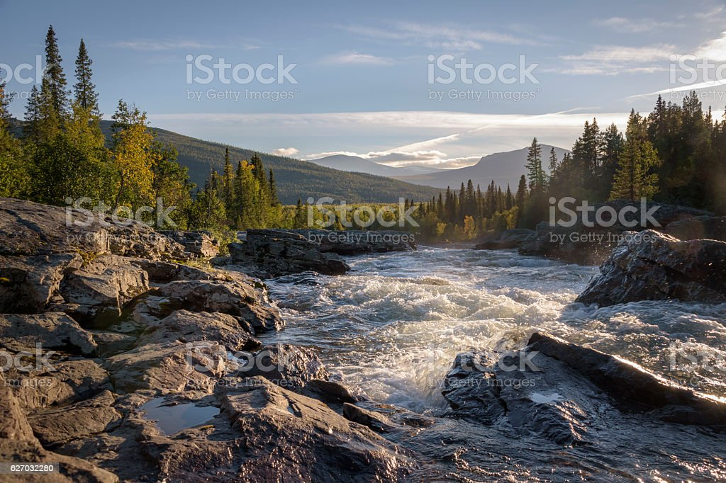 Golden light shining on wild river flowing down beautiful landscape stock photo