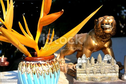 golden lion holds coins in its mouth against the background of an orange heliconia flower next to a sculpture of angkor wat in cambodia