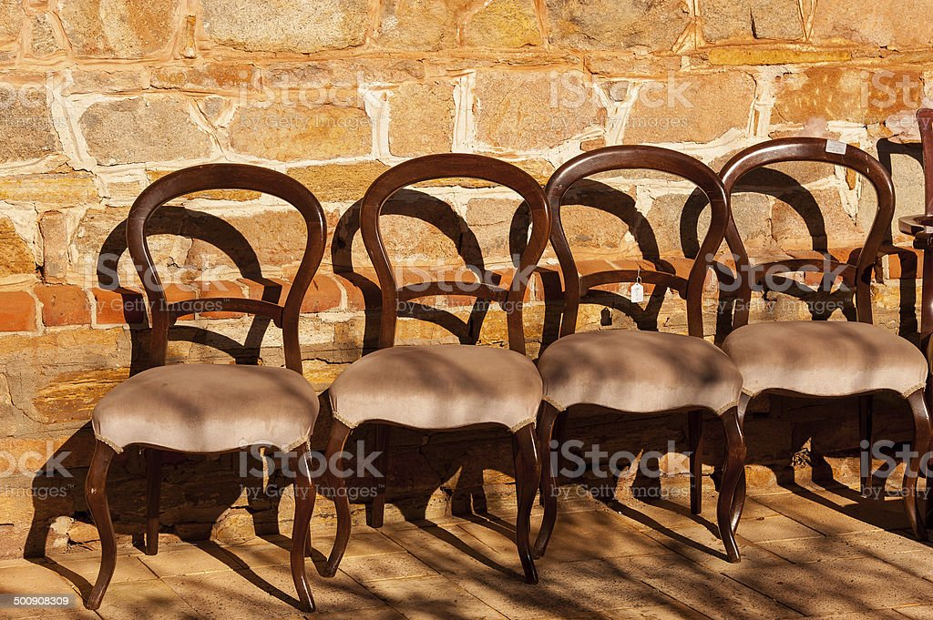Golden lit antique chairs for sale stock photo