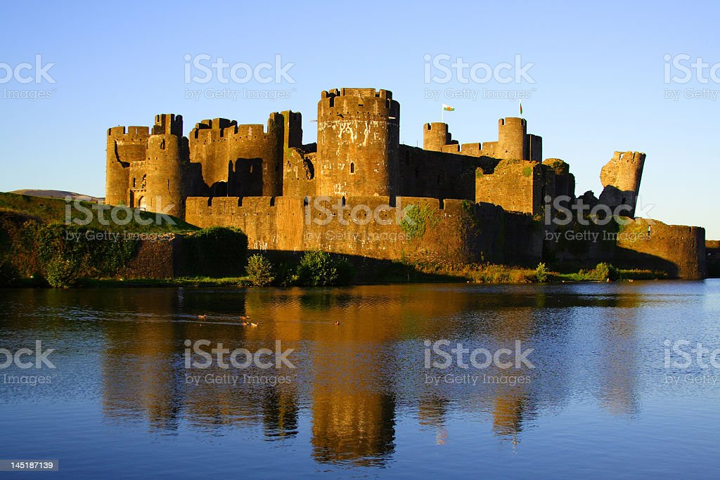 Golden lit Caerphilly castle with reflection in blue water royalty-free stock photo