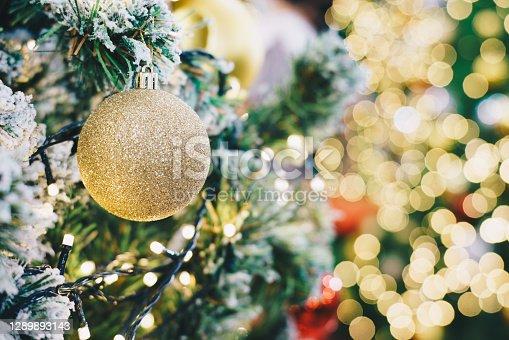 Golden luxury christmas ball hangging on pine tree blurred bokeh glitter background Xmas festival