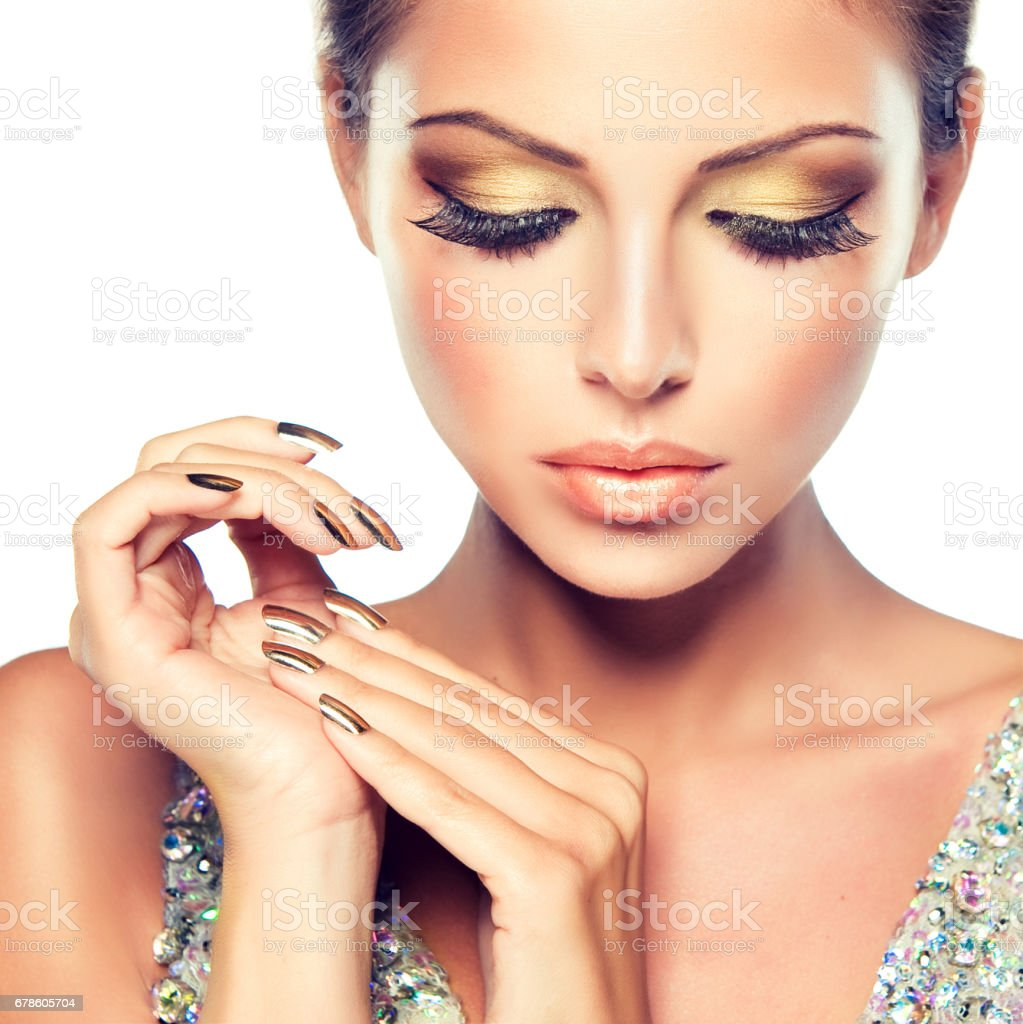 Golden make up, bright gilded manicure and elegant gesture. Close up portrait of attractive woman model. stock photo