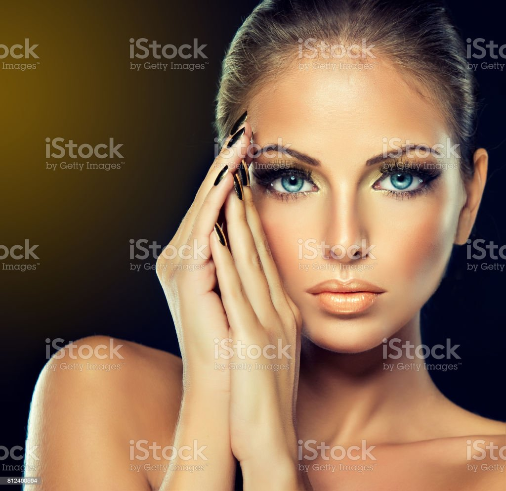Golden make up, bright gilded manicure and elegant gesture. Portrait of attractive woman model. stock photo