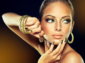 Beautiful woman-model with the golden makeup and gilded metallic manicure on the nails, dressed in golden earrings and bracelets. Fashion portrait.