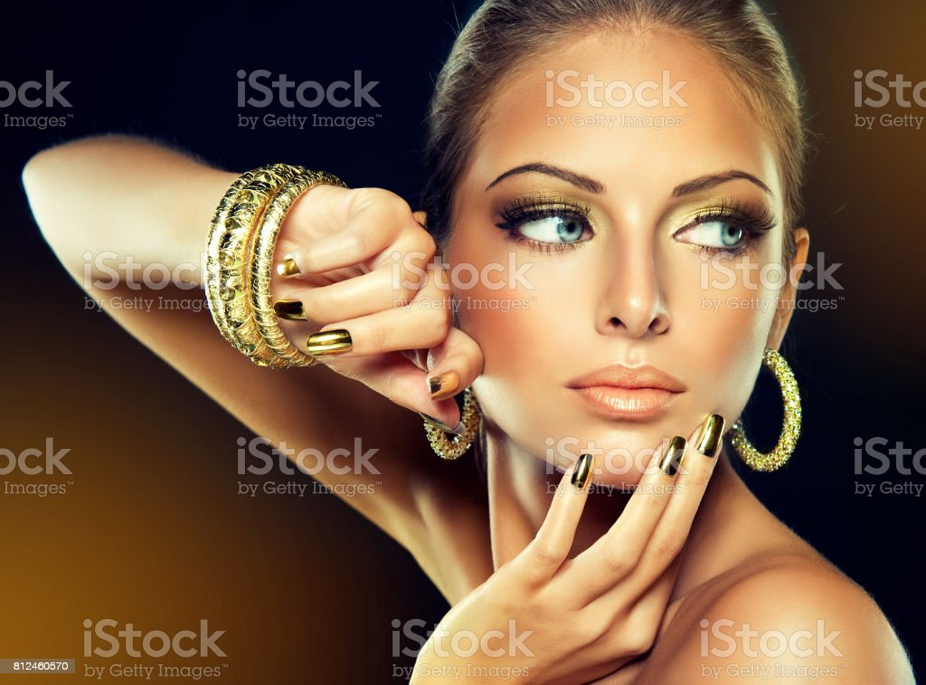 Golden make up, bright gilded manicure and elegant gesture. Portrait of attractive woman model in golden color.. stock photo