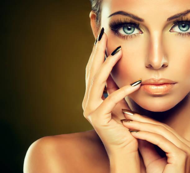 golden make up helle vergoldeten maniküre und elegante geste. porträt von attraktiven frau modell. - goldenes augen make up stock-fotos und bilder