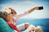 Senior couple on the sailing boat cruise taking selfie to remember this beautiful moment that they enjoy together.