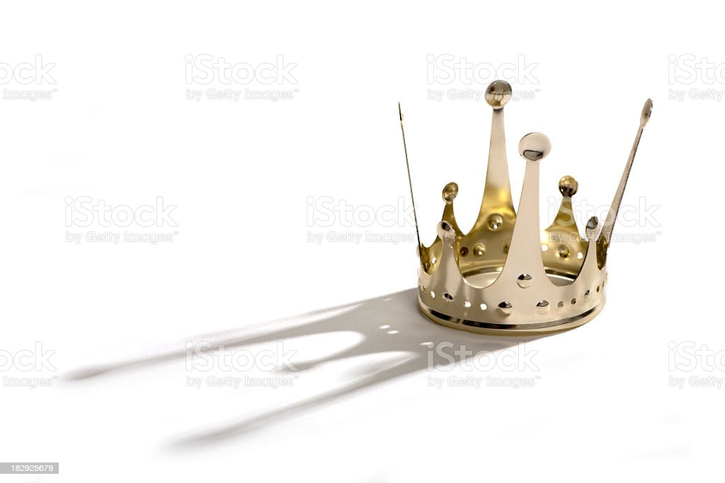 Golden metal crown casting grey shadow on white background stock photo