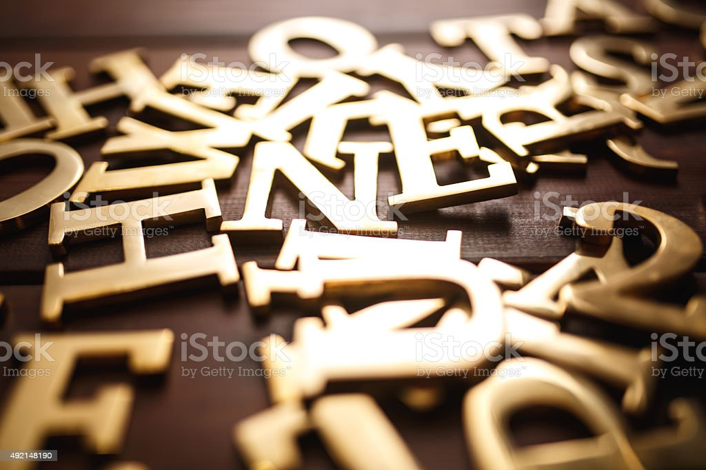 Golden metal letters on wood stock photo