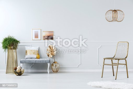 Golden metal net chair, creative design chandelier and an elegant upholstered bench in a bright apartment interior