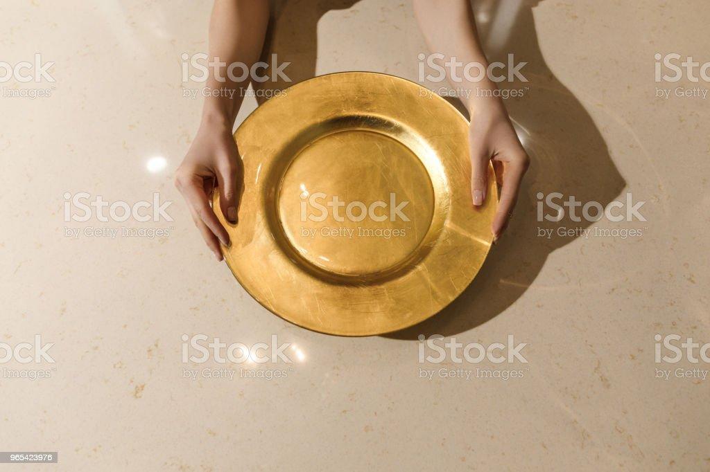 金金屬板材在女性手在輕的桌 - 免版稅一個人圖庫照片