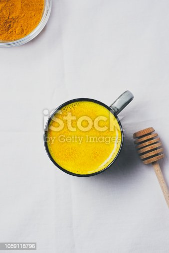 Golden milk with turmeric powder in cup over white background, flat lay top view. Detox healthy eating, energy boosting, flu remedy, natural cold fighting drink. dieting, weight loss concept, winter hot drink