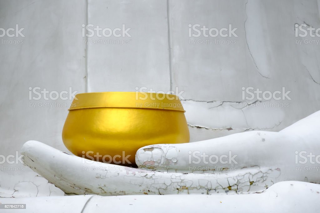 Golden Monk's Alms Bowl on Cracked Hand Statue stock photo