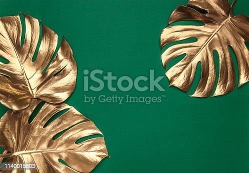 istock Golden monstera leaves on green background 1140015803