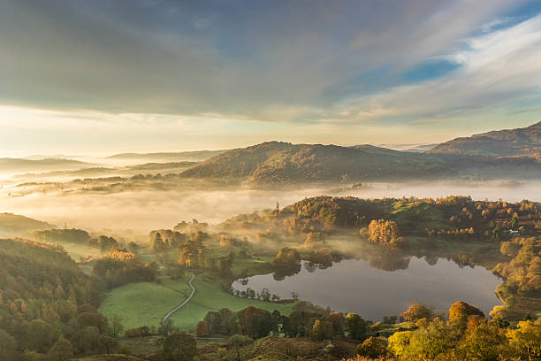 Golden Morning Light Shining Across Lingering Fog In Langdale Valley. A photograph taken from Loughrigg Fell in the English Lake District. The photograph features Loughrigg Tarn to the bottom right of the frame, beautiful lingering fog being lit by the morning sun and Lingmoor Fell in the background. The photograph was taken moments after sunrise on an Autumn morning. english lake district stock pictures, royalty-free photos & images