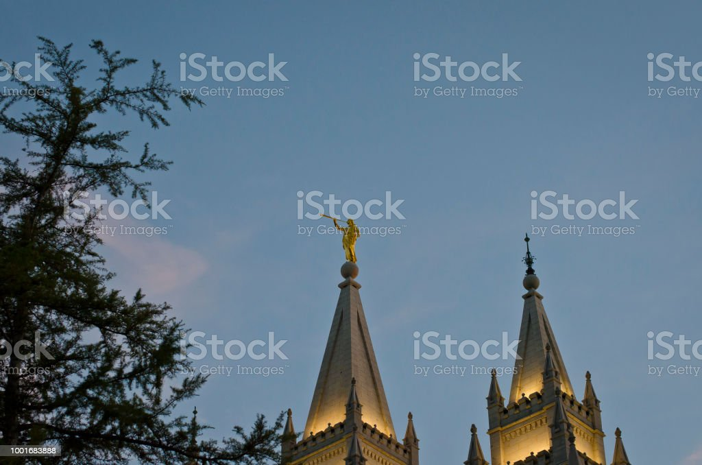 Golden moroni on the temple through the trees stock photo
