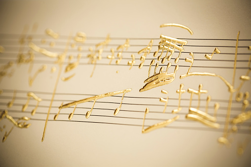close up of invented music notes made with golden handicraft work paste on textured paper,sepia toned and added noise