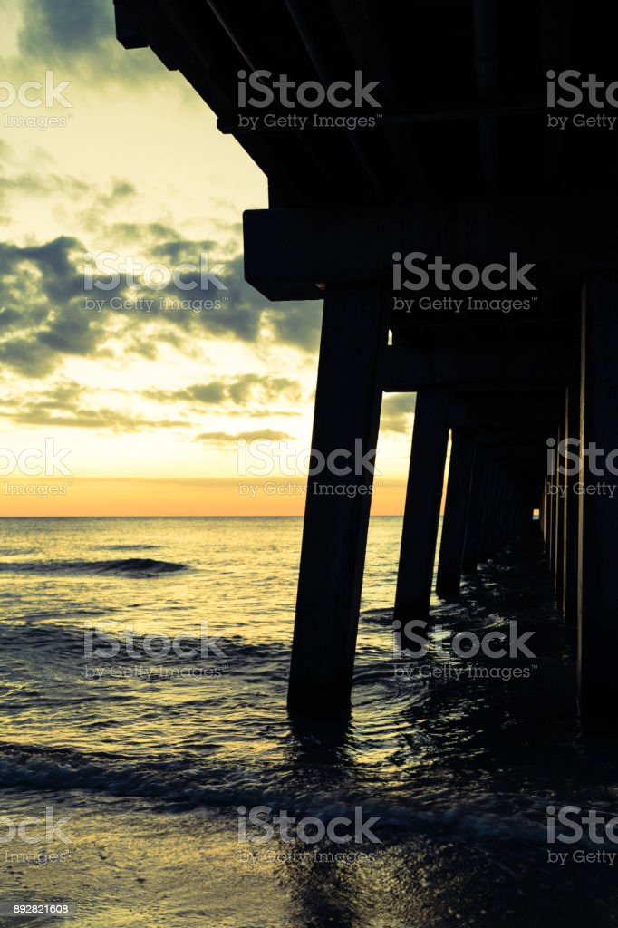 Golden Naples beach pier at dusk stock photo