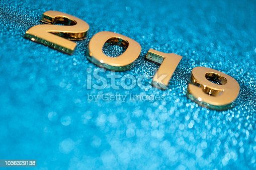 1018011484 istock photo Golden New Year 2019 on a sparkling bokeh background (blue) 1036329138