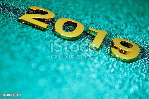 1018011484 istock photo Golden New Year 2019 on a sparkling bokeh background (aquamarine) 1048699120