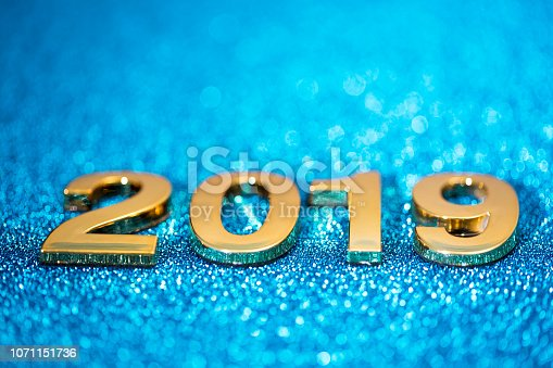 1018011484 istock photo Golden New Year 2019 on a sparkling defocused background (blue) 1071151736