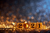 Golden numbers 2021 and Christmas decorations on glitter and defocused lights.