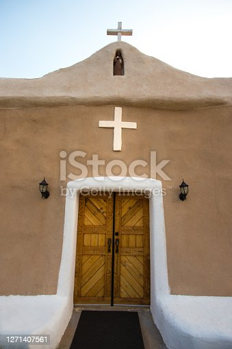 Golden, NM: The historic San Francisco de Asis Catholic Church. Golden is located 40 miles south of Santa Fe on the Turquoise Trail. Pale blue sky background and copy space.