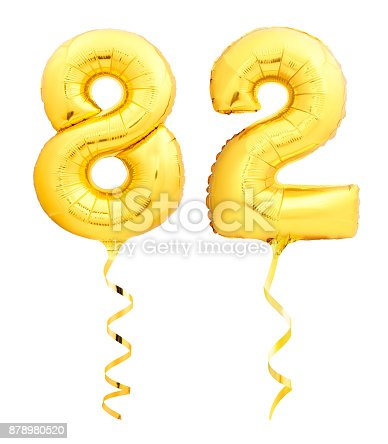 927069242 istock photo Golden number eighty two 82 made of inflatable balloon with ribbon on white 878980520