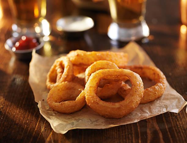 golden onion rings with beer in the background - gefrituurde uienring stockfoto's en -beelden