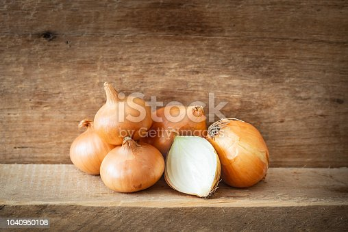 A heap of fresh golden onions on a wooden plank. One onion is cut and let see the white texture vegetable