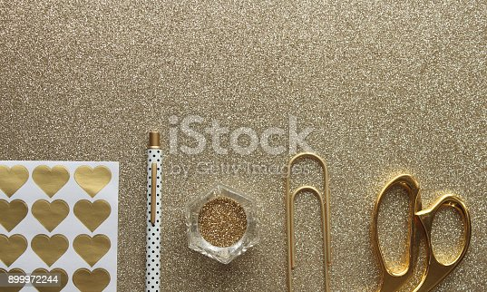 Gold office supplies against gold glitter background. Copy space.