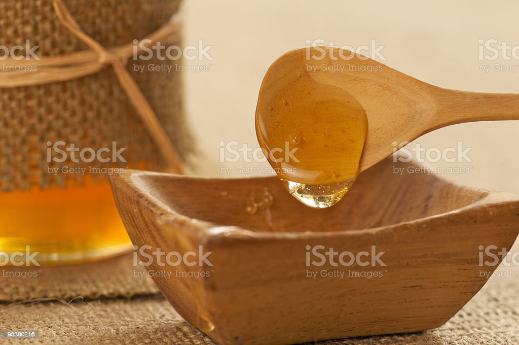 Golden Organic Honey Dripping off Wooden Spoon royalty-free stock photo