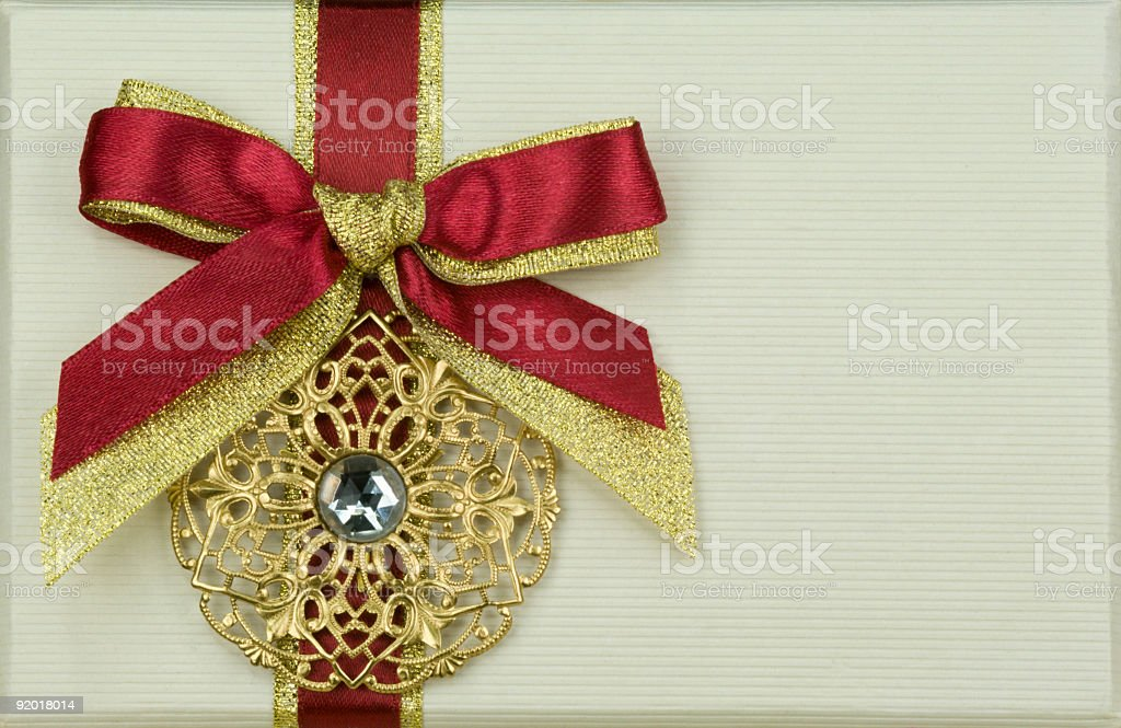 Golden ornament with bow on paper background royalty-free stock photo