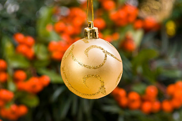 Golden Ornate Bauble in Front of Christmas Decoration stock photo