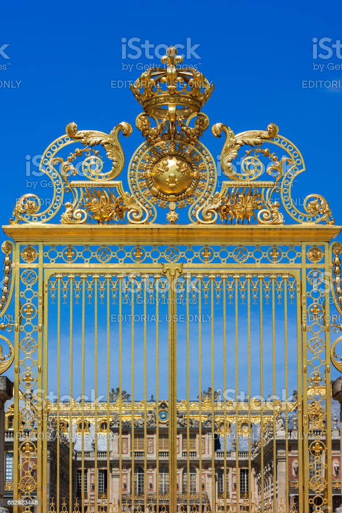 Golden ornate gates of the Palace of Versailles over blue sky. Paris, France stock photo