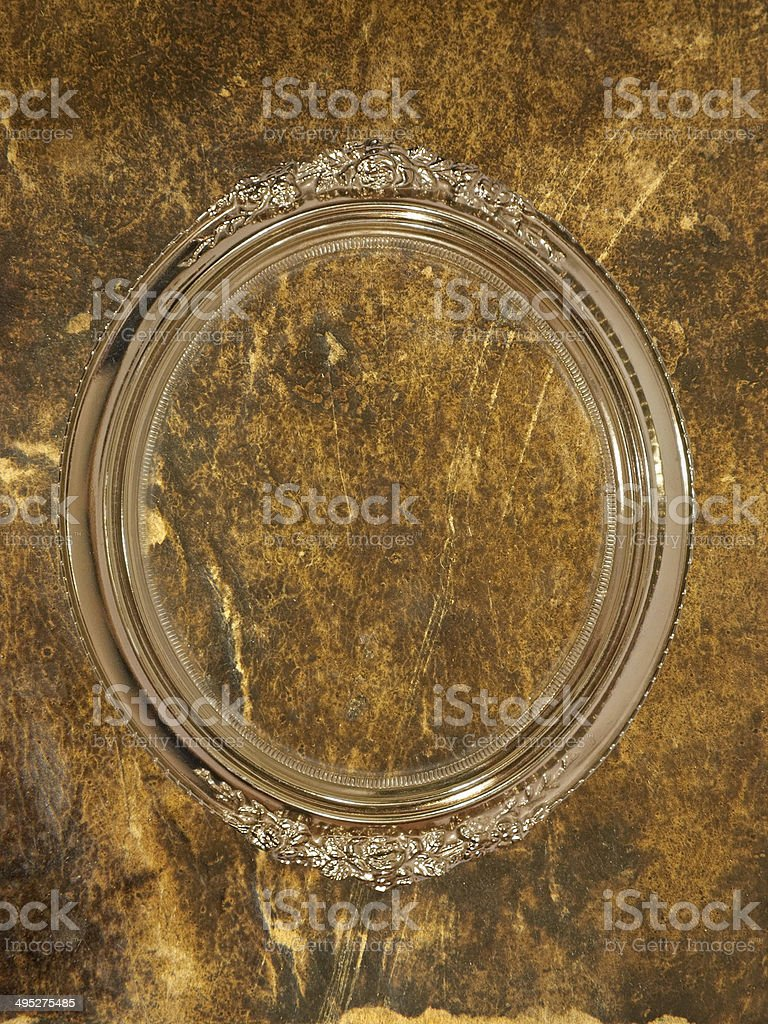 Golden oval photo frame on grungy wall. royalty-free stock photo