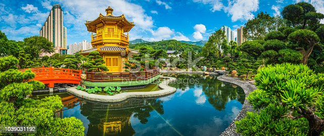 The ornate pagoda eaves and wooden footbridge of the Pavilion of Absolute Perfection in the green public parkland of Nan Lian Gardens, Hong Kong, China.