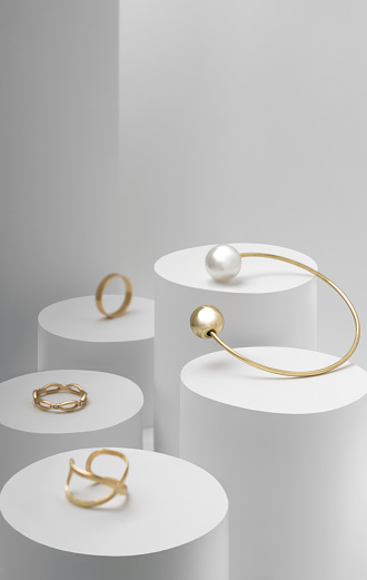 Golden pearl bracelet with golden rings collection on white cylinders vertical