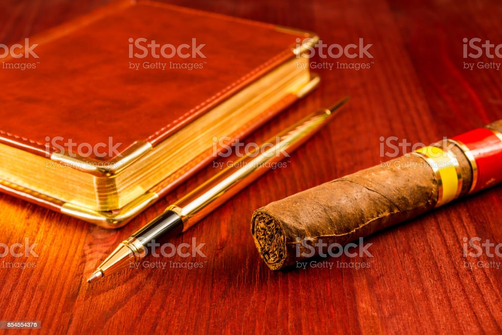 Golden pen with a leather diary and cuban cigar stock photo