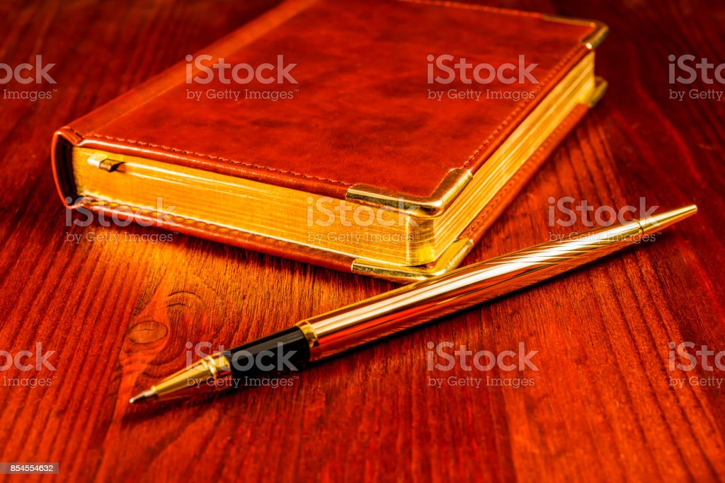 Golden pen with a leather diary stock photo