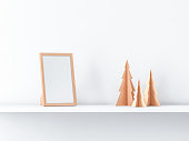 Golden photo frame Mockup on white shelf with paper christmas trees