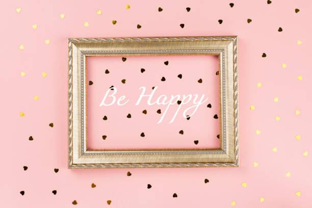 goldene bilderrahmen mit werden glücklich text, goldene konfetti auf pastell rosa hintergrund. valentinstag hintergrund - rosa zitate stock-fotos und bilder