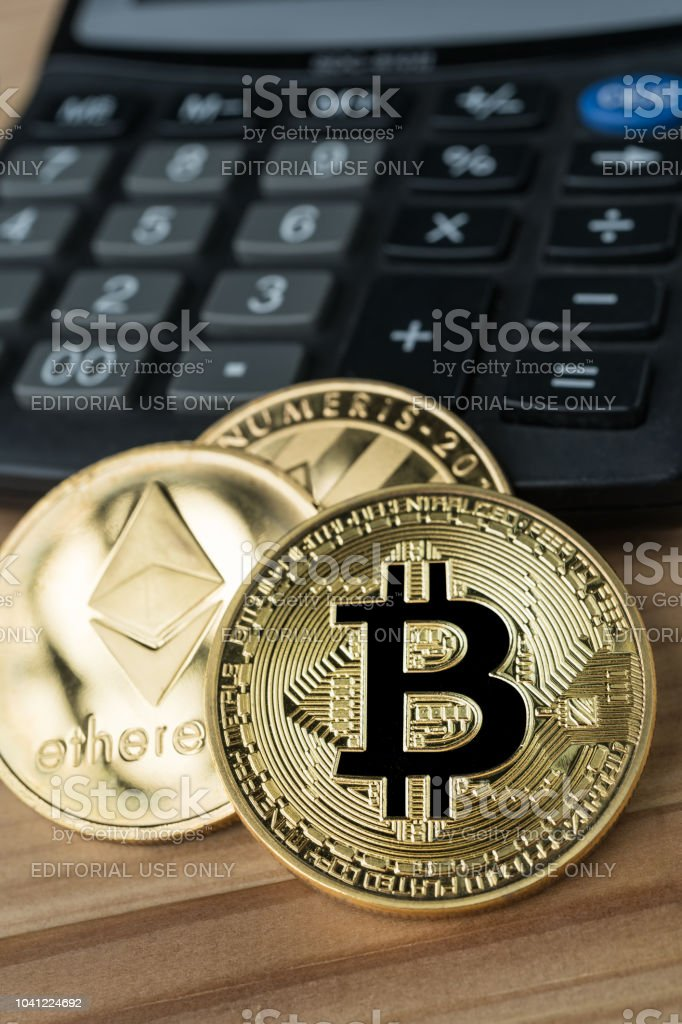 Golden Physical Bitcoin Ethereum And Litecoins On Calculator