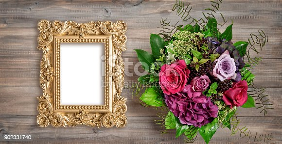 istock Golden picture frame and rose flowers. Vintage style mockup 902331740
