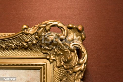 ornimental golden picture frame against a texture red brown wall