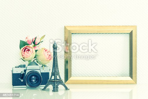 istock Golden picture frame, rose flowers and vintage camera. 482451214
