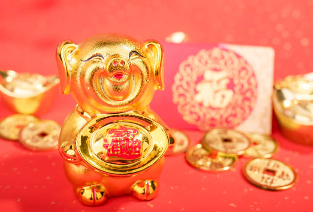 Statue de cochon doré sur fond rouge - Photo